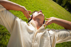 Man using headphones to sing along to music while lying in grass Stock Images