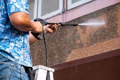 Man using High Power Pressure Water for Smash Cleaning Dirty Wall. royalty free stock image