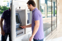 Man using his credit card in an atm Stock Photo