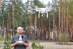 Man using his drone outdoor with forest background Royalty Free Stock Image
