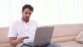 Man using his laptop and a credit card stock footage