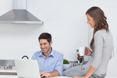 Man using his laptop in the kitchen Royalty Free Stock Photos