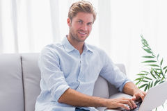Man using his laptop sat on the couch Royalty Free Stock Photo