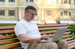 Man using his laptop in town. Middle-aged man sitting on a public bench in an urban square using his laptop in town Royalty Free Stock Photo