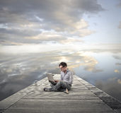Man using his laptop. Young man sitting on a dock using his laptop Royalty Free Stock Photography