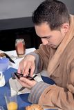 Man using his mobile at breakfast Royalty Free Stock Photography