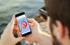 Man using his mobile phone on the coast with ads blocker. Man on the coast using his smartphone with ads blocker. All screen graphics are made up royalty free stock photos