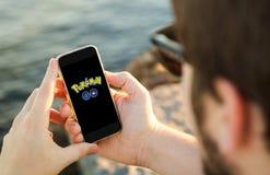 Man using his mobile phone on the coast with pokemon go logo on Stock Photo