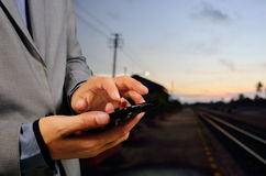 Man using his mobile phone on empty railway platform. Close-up h Royalty Free Stock Images
