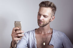 Man using his mobile phone. Happy young handsome male checking his cellphone stock photo