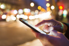 Man using his Mobile Phone in the street, night light bokeh. Close up of male's hands with smartphone in the city at night Stock Image
