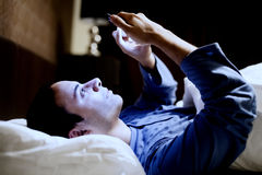 Man using his phone in the bed stock images