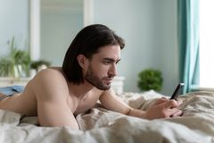 Man using his phone while he lying On Bed. In his home stock photos