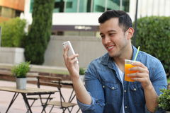 Man using his smartphone while enjoying a nice drink outside.  Stock Images