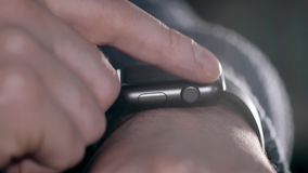 Man using his smartwatch. Close-up hands. In coffee bar a man using his smartwatch. Close-up hands stock footage