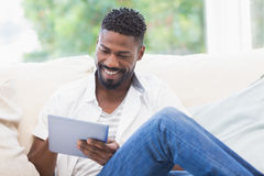 Man using his tablet on couch Royalty Free Stock Photo