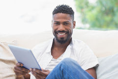 Man using his tablet on couch Royalty Free Stock Images