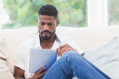 Man using his tablet on couch Stock Photos