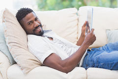 Man using his tablet on couch Stock Image