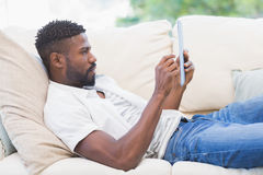 Man using his tablet on couch Stock Photography