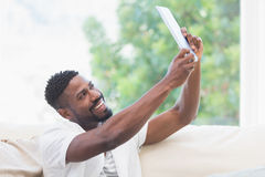 Man using his tablet on couch to take selfie Royalty Free Stock Image