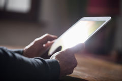 Man using his tablet,  hard light and flare effect Stock Photography