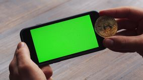Man using horizontal smartphone with green screen. Close-up shot of man`s hands with mobile phone and a gold bitcoin. Coin. Chroma key. Close up. Horizontal stock video footage