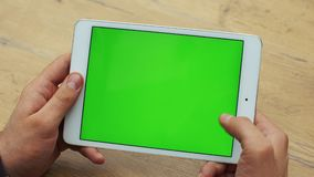 Man using horizontal tablet with green screen. Close-up shot of man`s hands with tablet. Chroma key. Close up. Horizontal stock video