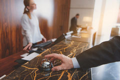 Man using hotel bell at reception Stock Photography
