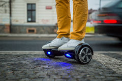 Man is using hoverboard against the background of leaving car stock image