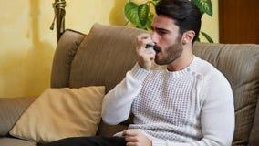 Man using inhaler on sofa