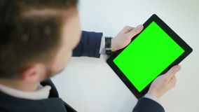 A Man Using an iPad with a Green Screen. Indoors. View from the top. Close-up shot. Soft focus stock footage