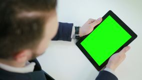 A Man Using an iPad with a Green Screen. Indoors. View from the top. Close-up shot. Soft focus stock video footage