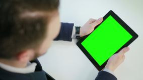 A Man Using an iPad with a Green Screen. Indoors. View from the top. Close-up shot. Soft focus stock video