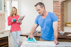 Man using iron while wife reading the news Stock Photography