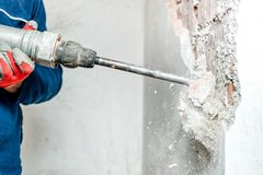Man using a jackhammer to drill into wall Royalty Free Stock Photo