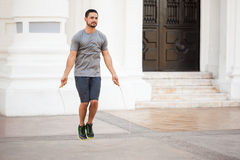 Man using a jump rope to exercise outdoors. Full length portrait of an athletic young man using a jump rope to exercise outdoors Royalty Free Stock Photography