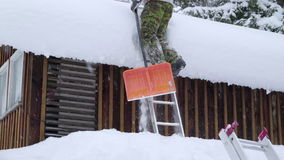 A man using the ladder to reach the snowy roof stock video footage