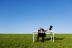 Man Using Landline Phone At Desk On Field Against Sky Royalty Free Stock Photo