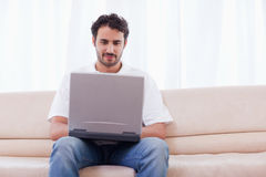 Man using a laptop. In his living room Royalty Free Stock Image