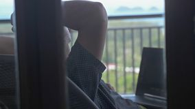 Young upset man using laptop in balcony at resort on vacation. slow motion. 3840x2160. Man using laptop in balcony at resort on vacation stock footage