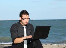 man using laptop at beach Stock Photography