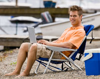 Man using laptop on beach Royalty Free Stock Photo
