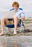 Man using laptop at beach Stock Image