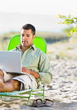 Man using laptop at beach Stock Images