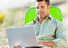 Man using laptop at beach Royalty Free Stock Photos