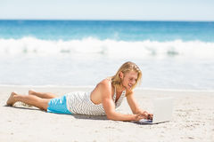 Man using laptop on beach Stock Photo