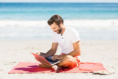 Man using laptop on beach Stock Photography