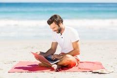 Man using laptop on beach Stock Photos