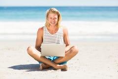 Man using laptop on beach Stock Image